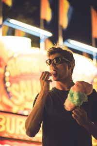 Young man eating cotton candy